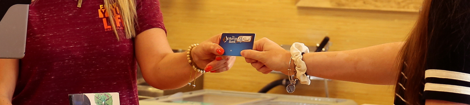 woman handing person a credit card