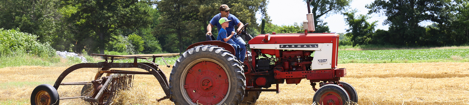 Man teaching his son how to drive a tractor