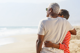 man and woman hugging on beach