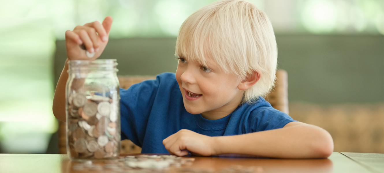 kid putting change in jar